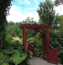 An ornamental gate leads into a lush garden at Lost Horizons