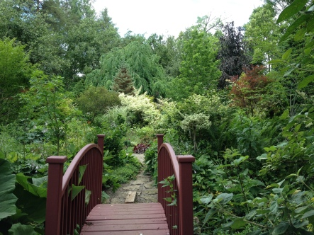 A garden bridge leads into a garden filled with inspiring plantings.