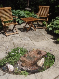 Two folding wooden chairs provide garden seating next to a small water feature in an urban garden.