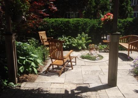 Wooden garden seating around a small water feature in an urban garden.