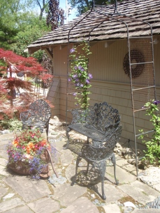 Formal garden seating furnishes a small area between a house and garage.