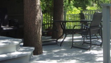 A white painted wooden deck incorporating large trees creates a cooler backyard.