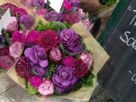 A bouquet of roses, mums and small ornamental cabbage heads with a fall decor theme.