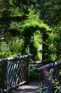 A wooden bridge and arbour showing garden design blending with nature at Reford Gardens.