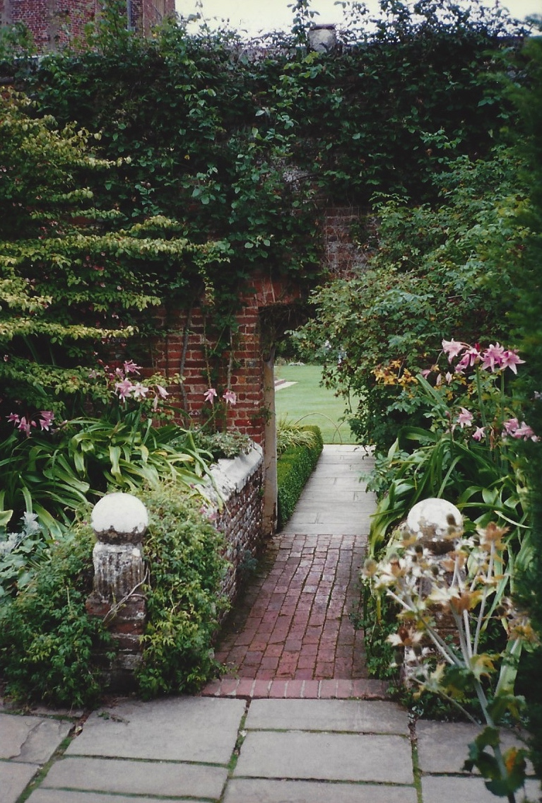 An archway in an old brick wall leads from one garden room to another.