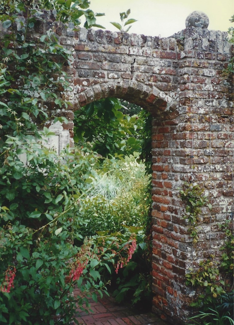 A wall with an entrance leading from one garden room to another.
