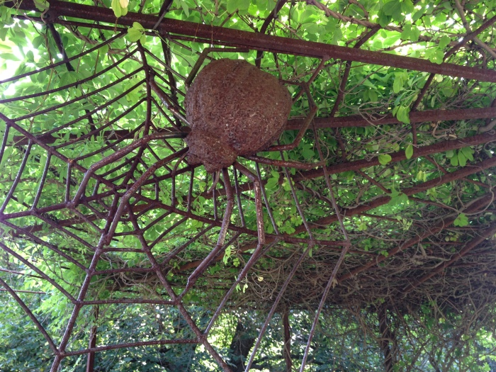 Metal spider sculpture with web-shaped pergola.
