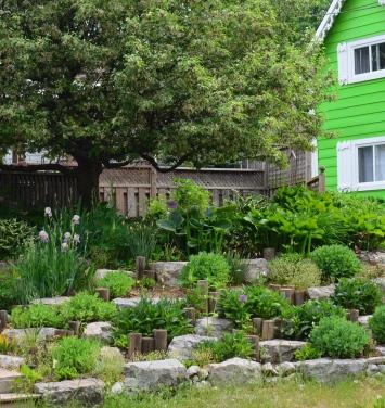 Vertical logs create interest in a garden bed.