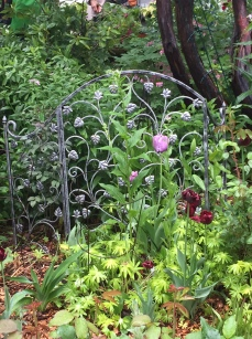 A flowery fire screen creates interest in a flower bed.