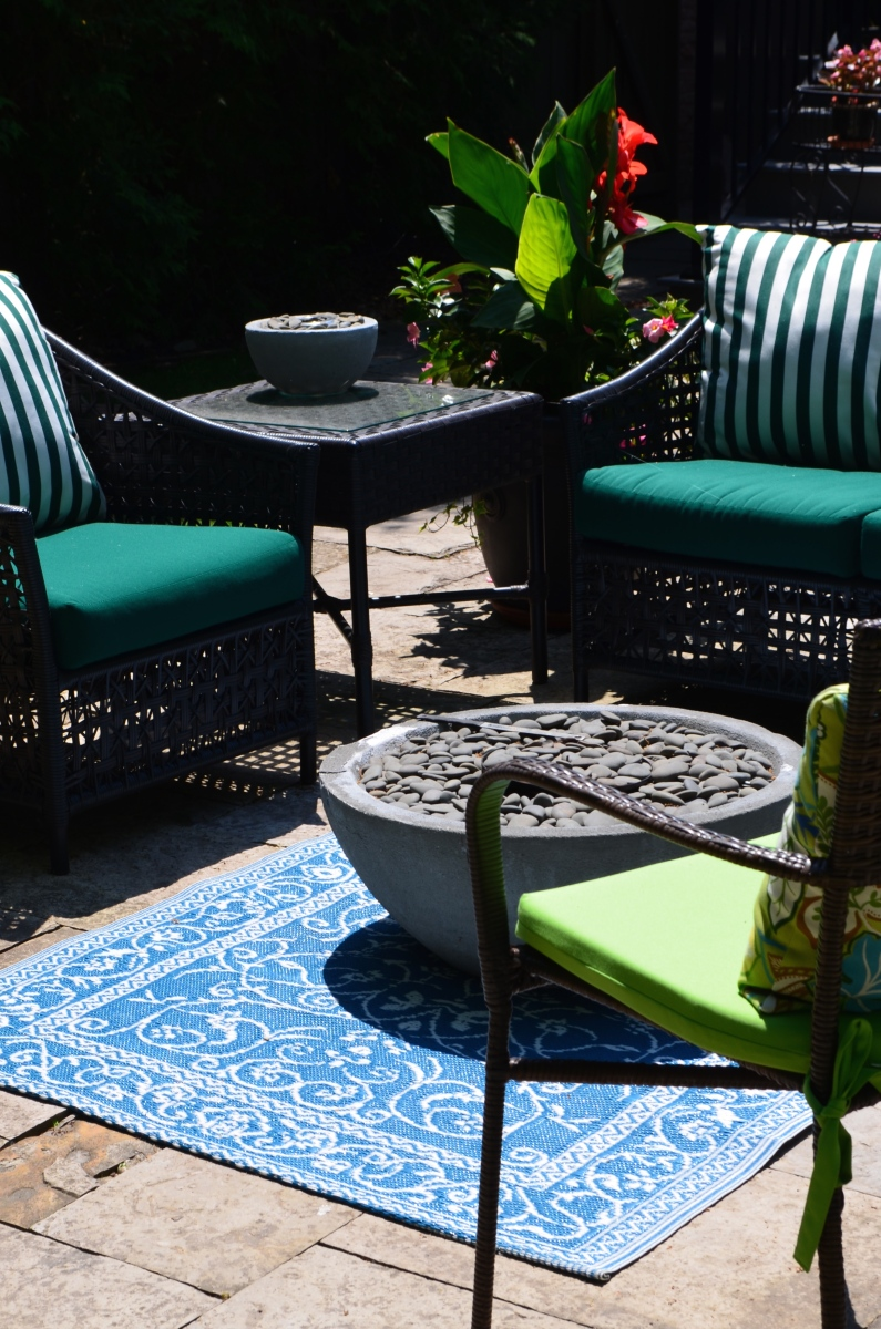 An outdoor carpet brings outdoor furniture in a garden together as a focal point.