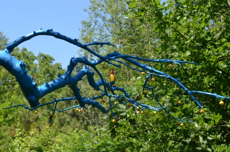 A dead tree branch painted blue is decorated with a painted bird.
