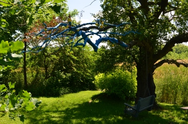 A dead branch painted blue becomes a garden focal point.