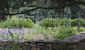 A walled garden gets added height with plant supports.